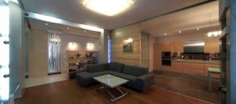 Темный угловой диван в центре гостиной