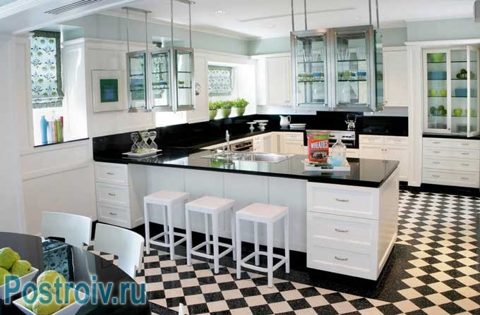 Большая кухня в черно белом цвете. Пол выложен плиткой как шахматная доска
