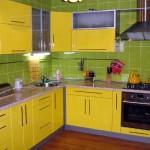 Зеленый кухонный фартук на желтой кухне. Фото 11