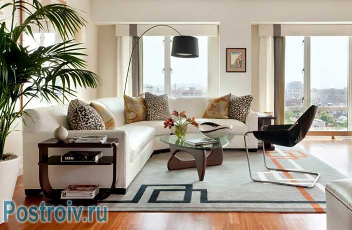 Белый большой угловой диван и стеклянный столик в светлой гостиной