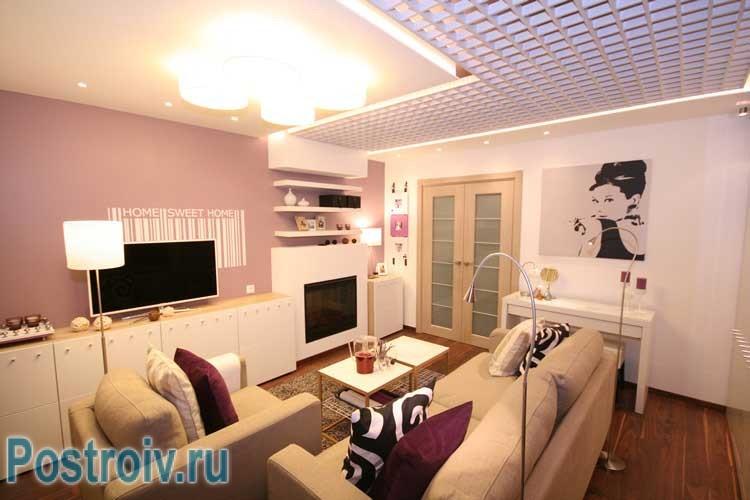 Бежевый диван в центре гостиной. Фото