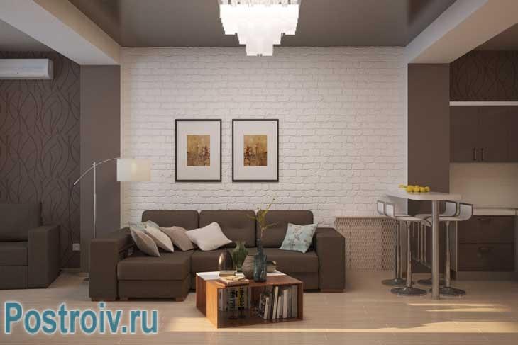 Стена гостиной отделана декоративным кирпичом. Также присутствуют модульные картины - Фото