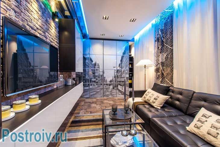 Прямоугольная гостиная отделанная в стиле лофт. Маленький столик возле дивана дает законченный вид - Фото