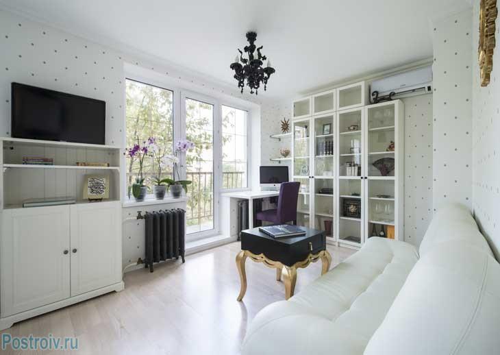 интерьер однокомнатной однушки в панельном доме. Обои белого цвета. Черные элементы декора. Фото