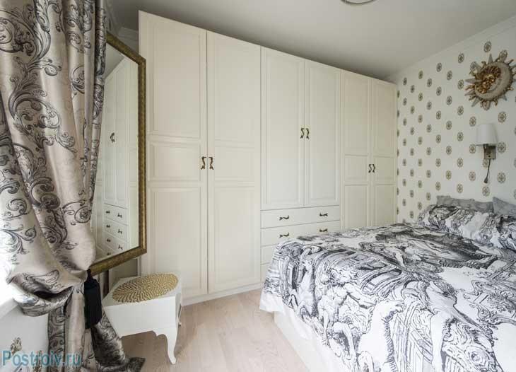 Интерьер спальни. Большое зеркало в золотой оправе. Красивый белый шкаф практически во всю стену. Фото