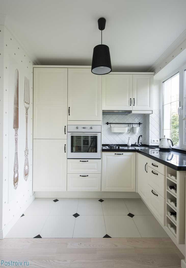 Угловая кухня в панельном доме. Белые фасады, черная столешница из искусственного камня. Фото ремонта