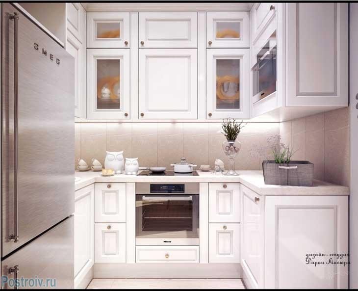 Очень маленькая белая кухня с серебристым холодильником. Фото