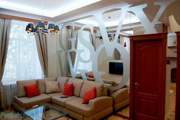 Зеркальная стена с рисунком в гостиной. Фото