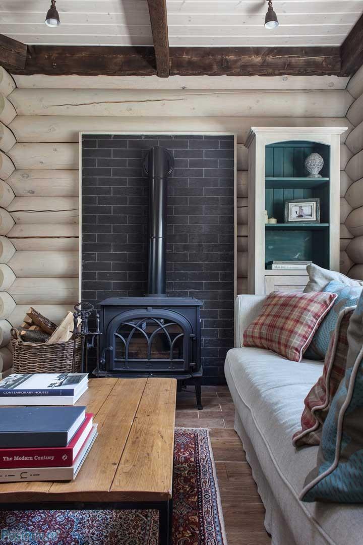 Настоящая печка с дровами в гостиной загородного дома. Темные балки на потолке и белые стены сруба. Фото