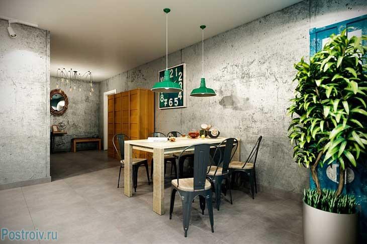 Обеденная зона. Прямоугольный светлый стол и черные стулья. Зеленые светильники. Фото
