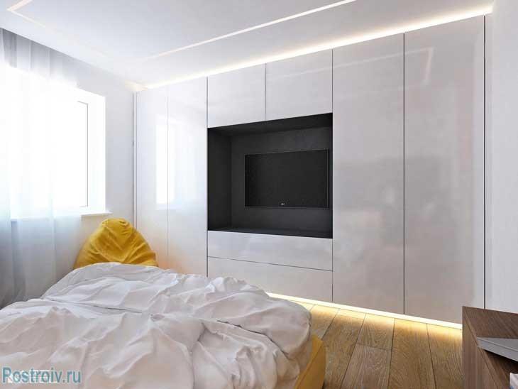 Белый глянцевый шкаф в спальне с вырезом для телевизора. Фото