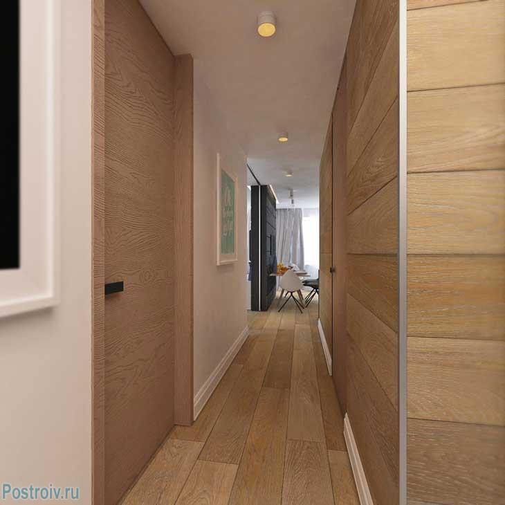 Коридор в двухкомнатной квартире. Стены отделаны ламинатом. Фото