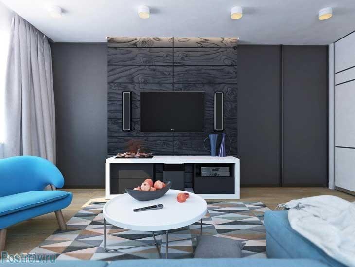 Телевизор на стене в гостиной и под ним белая тумба. Фото