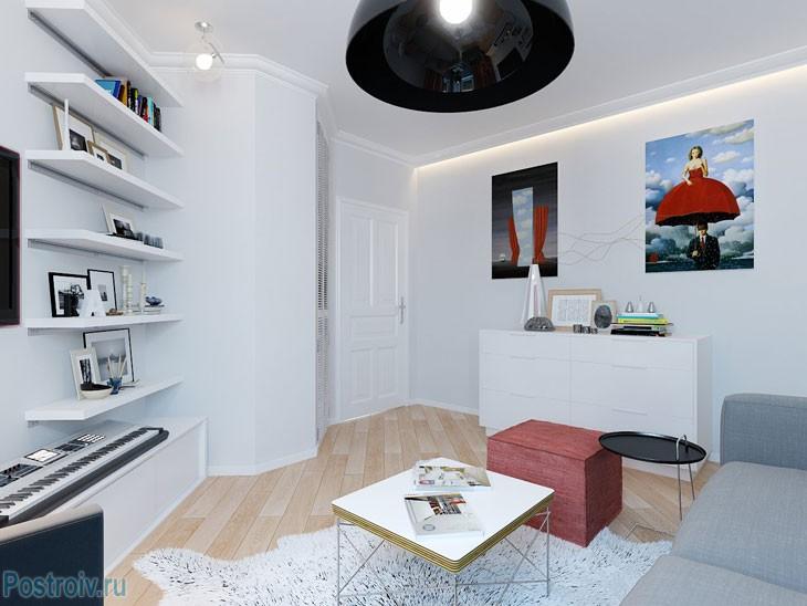 Белый стены и ярки картины на стене в комнате однокомнатной квартиры. Фото