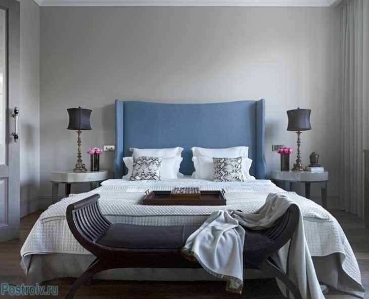 Серые стены в спальне и голубое изголовье кровати. Фото