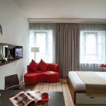 Красный диван в однокомнатной квартире. Фото