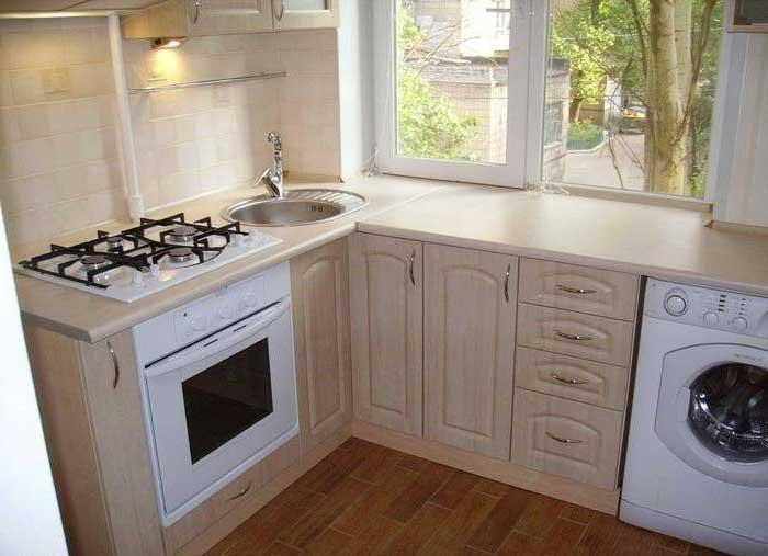 Стиральная машинка на кухне под подоконником