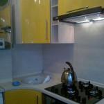 Желтая угловая кухня с варочной панелью с колонкой
