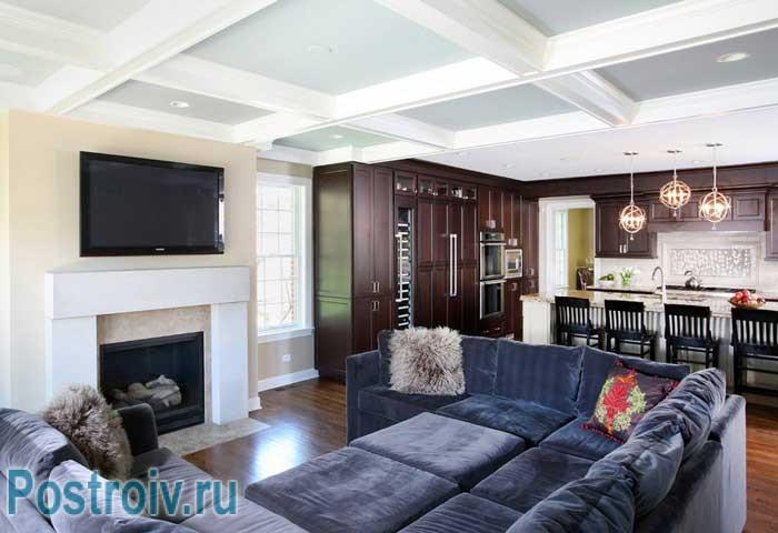 Синий бархатный диван в гостиной с декоративным камином