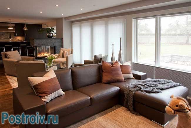 Темный классический кожаный угловой диван в гостиной