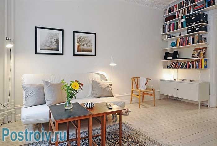 Белые стены оформленные краской. На полу гостиной паркет
