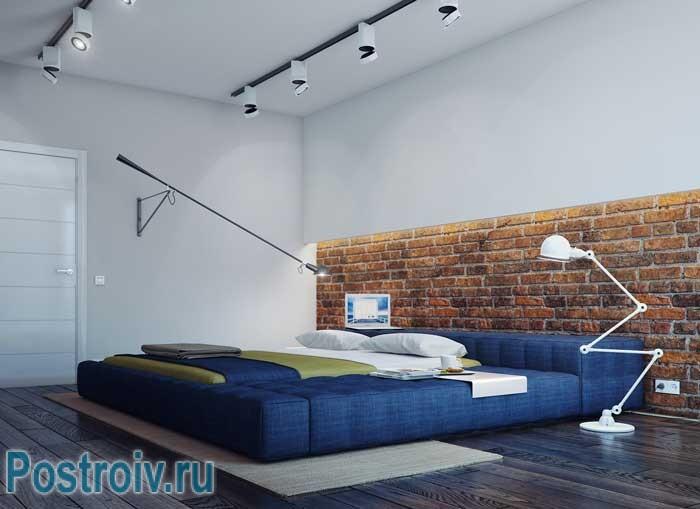 Современный дизайн второй спальни с кирпичной стеной в квартире в стиле лофт