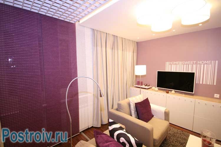 Плотные шторы молочного цвета в гостиной-спальне. Фото