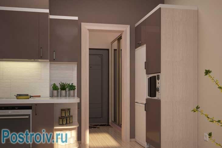 Зона кухни в квартире студии визуально зонирована с помощью декоративных колон - Фото