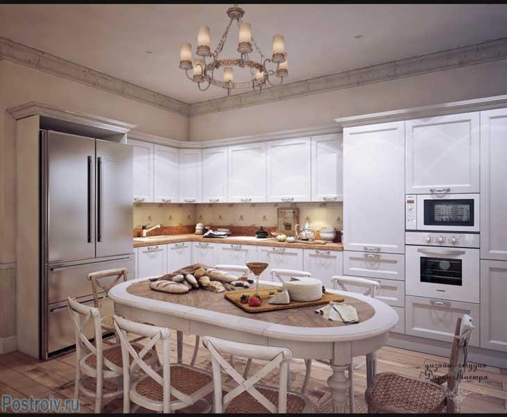 Большая угловая белая кухня с овальным столом для всей семьи. Фото
