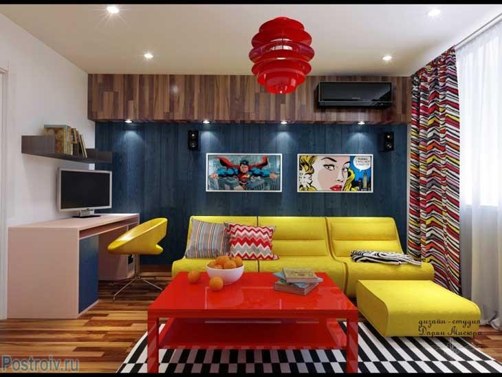 Желтый угловой диван и красный журнальный столик в гостиной, красный светильник. Фото