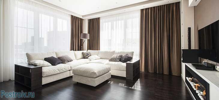 Большой белый угловой диван в сочетании с темным полом. Фото