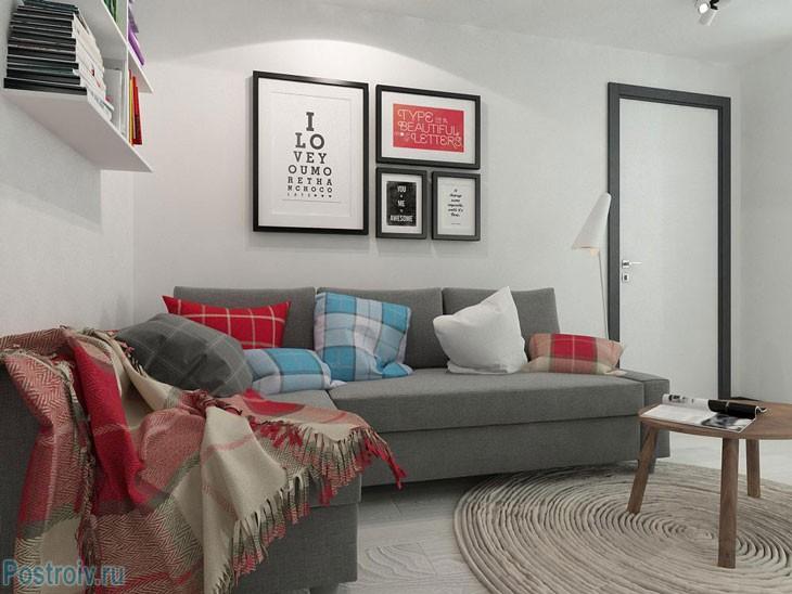 Серый диван. Декорирование стены рамками разных размеров. Фото