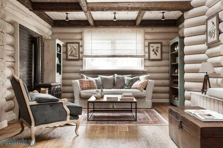 Интерьер загородного дома. Зона гостиной. Белый диван буфеты и журнальный столик в ретро стиле. Фото