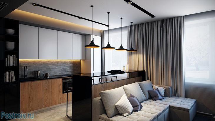 Серый угловой диван в совмещенной кухне с гостиной. Фото