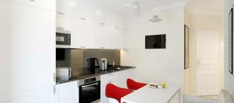 Белые стены и красные акцентные стулья на кухне. Фото