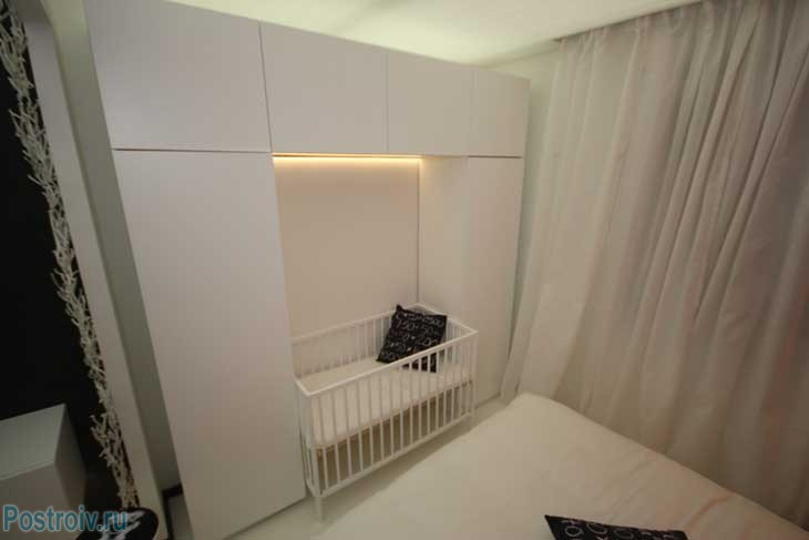 Спальня в гостиной с кроваткой для ребенка. Фото