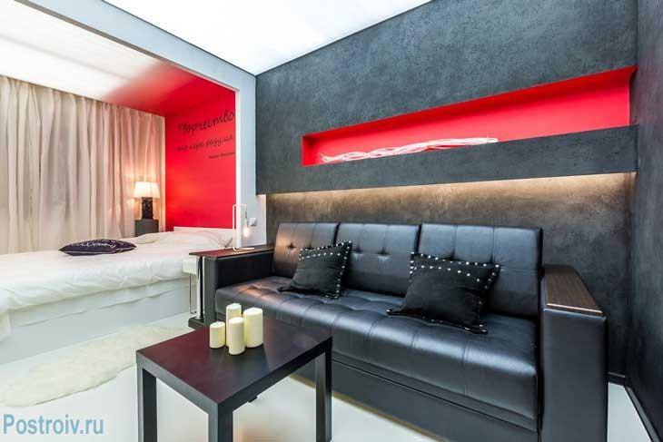Зона гостиной с черным диваном и черными стенами. Фото
